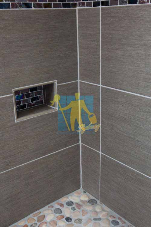 large format dark porcelain tile on shower walls with grey grout lines